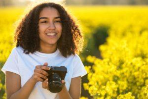 donna con macchina fotografica in un bellissimo prato fiorito - content marketing per ecommerce